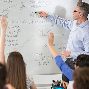 Male teacher leading physics lesson at whiteboard in classroom.